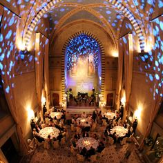 Silver and blue spotlights illuminate the reception venue, immaculately turned out in pure white flowers, candles and linens