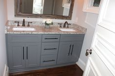 Grey Shaker cabinets with oil rubbed bronze pulls and faucets. Dallas White granite