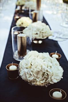with white pillar candles and gold tea light holders. varying flowers in the mix of the hydrangeas