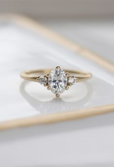 Drawing inspiration from our classic Three Stone Ring, this delicate multi-stone engagement ring is the perfect mix of modern, minimal, and feminine. The perfect counterpoint to a wide variety of wedding band styles, this ring is as versatile as it is pre Gold Diamond Wedding Band, Diamond Bands, Diamond Engagement Rings, Wedding Bands, 1920s Engagement Ring, Stacked Wedding Rings, Wedding Rings Simple, Trendy Wedding, Goals Tumblr