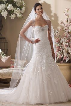 <strong class='info-row'>David Tutera for Mon Cheri</strong> <div class='info-row description'>214219 - Picabo  2014 Collection – Strapless lace appliqué, tulle and sequin over satin full A-line wedding dress, sweetheart neckline and curved back bodice adorned with hand-beaded jeweled trim, dropped waistline, lace appliqués accented with sequin cascade down to baby hemline and chapel length train.</div> <div class='row info-row text-center'> <div class='col-xs-6 col-xs-offset-3'> <a…