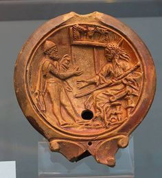 Oil lamp with a scene of Odysseus standing in front of Circe; the sorceress is wearing a rich cloak; she is sitting on a chair and holds a staff with her left hand. In the background the heads of three horses inside a stable are visible.