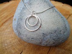 Ce collier simple et élégant est entièrement à la main en argent sterling. Elle est faite de deux anneaux de tailles différentes, maintenues ensemble par un anneau plus petit. Les deux plus grands anneaux ont été faites de fil dargent sterling de 1mm.  Le pendentif est suspendu à une chaîne en argent sterling. Le collier peut être équipé dune chaîne soit un 16 ou 18 pouces en série. Toutefois, si vous désirez une chaîne plus longue, sil vous plaît laissez-moi savoir.  Taille : de chaine en…