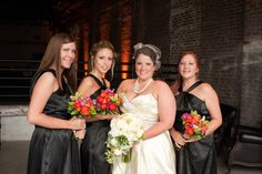 This bride accessorized her modern black and white wedding with pops of color in her bridesmaid's bouquets. Her girls are wearing David's Bridal's y-neck charmeuse # bridesmaid dress with a flirty bubble hem.  Style 84177 in Black.