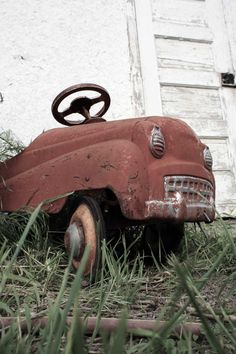 Rusty pedal car. Imagine the little boy who use to ride this toy car. Happy memories.