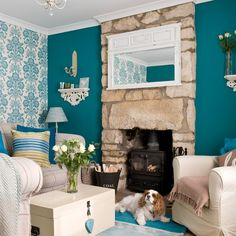 Love the contrast between the bold teal block colour, the intricate patterned wallpaper and rustic stone fireplace