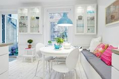 wiszące białe witrynki, okrągły stół i ławka z poduszkami w skandynawskiej jadalni z niebieską lampą