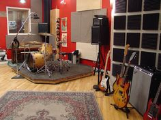 nice practice room with a little drum riser guitar room