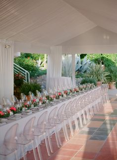 Outdoor romantic modern destination wedding with acrylic ghost chairs and coral flowers: http://www.stylemepretty.com/2016/09/28/an-azur-coral-destination-wedding-on-the-french-riviera/ Photography: Greg Finck - http://www.gregfinck.com/