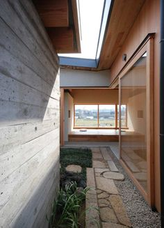 Kishigawa Residence, a tiny 49.6 m2 (534 ft2) courtyard house by Mitsutomo Matsunami.  The house has a U-shaped floor plan arranged around a small courtyard, with the garage sitting on the fourth side. There is no wall on the courtyard side of the garage, allowing for the requested views from the house through the courtyard and into the garage. The courtyard serves as the entry point to the small home.