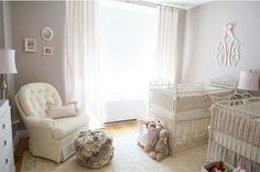 Quarto de bebê com enxoval rosa suave de gêmeas com berço de ferro no estilo clássico.