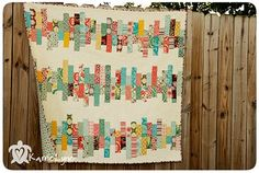 Scrappy quilt. Scrap strips set together with muslin. Greens and reds. etc.