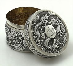 "A round Chinese silver box with chased dragons and clouds on the body and lid. Marked on the underside 90 and KK. Height 2 1/4""; Diameter 3""; weight 3.65 troy oz. Monogrammed in the carouche on the lid. The interior is gold washed."