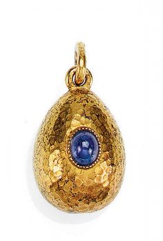 A FABERGÉ JEWELLED GOLD EGG PENDANT - AUGUST HOLLMING, ST PETERSBURG, 1899-1908   1899-1908  height: 1.5cm, 5/8 in  the surface hammered and set with a cabochon sapphire, 56 standard  PROVENANCE  The Kazan Collection  LITERATURE  M. Ghosn, Objets de Vertu par Fabergé, 1996, no. 196, illustrated.