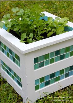 Turn a wooden planter into something special by adding a fresh coat of paint and some colorful tiles. || @splendidamy