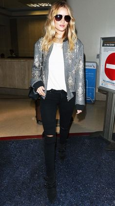 Rosie Huntington-Whiteley wears a printed bomber jacket, skinny jeans, suede ankle boots, and aviator sunglasses