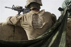 The tattoo of a U.S. Marine from the 2nd MEB, 1st Battalion 5th Marine, is seen through a hole on the back of his uniform shirt, as he stands guard at a compound in the Nawa district of Afghanistan's Helmand province, Wednesday, July 8, 2009