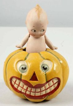 Kewpie Doll in a Jack O'Lantern ~ This is an unusual pairing, an adorable Kewpie doll in a paper mache jack o'lantern. Doll is removable from pumpkin. Has original paper label on bottom side of jack-o-lantern indicating copyright Rose O'Neill