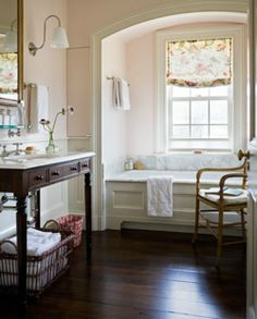 Love the wide plank floors in this bathroom, and how the dark wood contrasts with the light pink walls, off white millwork, and Carrara marble. The work of Gil Schafer.