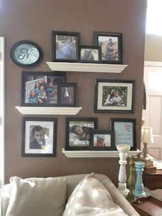 Floating shelves picture display. I like the white shelves, black frames and dark wall,