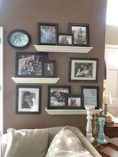 Floating shelves picture display. I like the white shelves, black frames and dark wall,