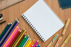 blank notebook colorful pensils and stapler on wooden desk for any