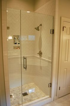 white subway tile love the mix of layout of tiles and the frame less glass shower door