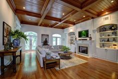 Luxury living room with large l shape sectional sofa wood floors wood beam ceiling and built in bookcase with fireplace