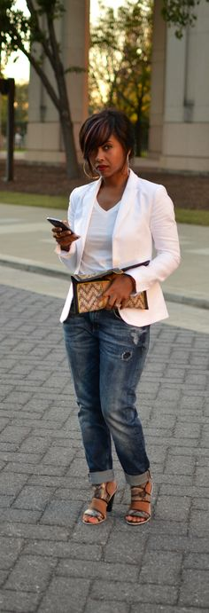 Very trendy -- pegged 'boyfriend' type jeans with small rips, strappy heels, a casual white tee and a crisp white blazer -- with a clutch purse.