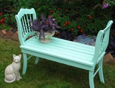 Two matching dining chairs are joined together with a wooden platform to make a wonderful garden bench