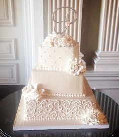 Vintage and modern is the best way to describe this all cream wedding cake. The buttercream wedding cake is made of three square layers and fondant white roses. The top and bottom layers of this wedding cake are decorated with beautiful patterns and swirls. Wow. Products by Palermo's Custom Cakes & Bakery