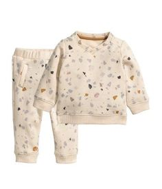Light beige/patterned. BABY EXCLUSIVE/CONSCIOUS. Set with a top and pants in organic cotton sweatshirt fabric with a printed pattern. V-neck sweatshirt with