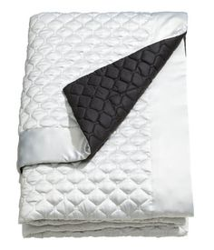 Quilted bedspread with polyester satin at front, woven cotton fabric at back, and polyester padding.