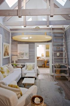 Ladies Street - Beach Style - Family Room - Jacksonville - Starr Sanford Design, wood panel walls, fur rug, white furniture, yellow accents, surf board, ladder, loft