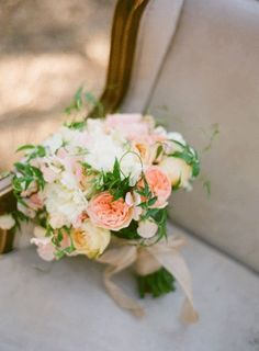 The bridesmaids will carry clutch bouquets of cream hydrangeas, peachy Juliet garden roses, coral ranunculus, jasmine vine, and seasonal greenery wrapped in navy blue ribbon with the stems showing.