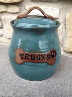 Dog treat jar canister handmade on pottery wheel. Imagine this cute little pet canister sitting on your counter top waiting to reward your pup! This dog treat jar is colored in an intense, food safe, opaque blue-green glaze over hazelnut stoneware. On this dog treat jar, the bone handle and name plate are left un-glazed for a beautifully rustic look. Your one-of-a-kind, hand-thrown pet treat canister can be personalized with your pets name instead of treats at no additional charge (up to 8…