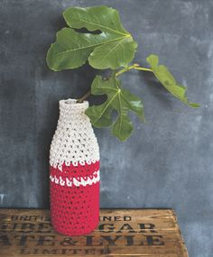 Bottle Vase by Stella Melgrati.   Founded on a love of natural yarns and fabrics — wool, cotton, hemp and linen — Stella Melgrati's company, the Yarn Kitchen, celebrates these simple materials in all their forms.   This project uses a milk bottle covered with chunky cotton rope in two contrasting colours to create a crocheted vase. Inspired by crocheted bottle covers popular in the 1960s, the design combines simple materials to celebrate an everyday object.