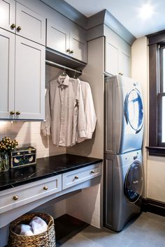 This traditional laundry room boasts a beautiful, updated design. Built-in cabinets prevent clutter and create a polished look paired with black marble countertops. A rack keeps hanging clothes neat and out of the way.