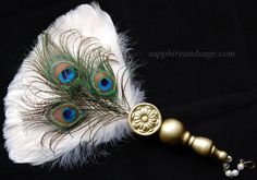 """Catriona Renaissance Feather Fan www.sapphireandsage.com  Sleek and shiny hackle feathers in a vibrant hue, sure to draw attention wherever you go! This rooster feather and peacock eye Renaissance fan showcases a hand-crafted wooden handle, topped with a 1.25"""" floral motif wood medallion."""