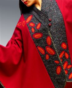 Handmade, one of a kind, red cape by Lorraine Jackson. The textiles in each garment are manipulated using layers of fabrics which have been couched, pin-tucked, appliqued and carefully top stitched into graphic shapes and designs, with significant attention to details.
