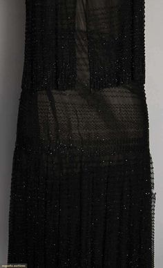 """LOUISE BOULANGER BEADED DRESS, 1920s. Black tulle covered in rows of small black jet beads, skirt gathered below hip, top w/ waist length beaded flounce, low scoop F & B neck, black silk underdress, label """"LOUISE BOULANGER Champs Elysees 3. Rue de Berripa Paris"""". Detail"""