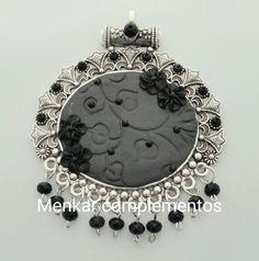 Colgante tipo medallón de 7,5 x 9,5 cm. Elaborado en arcilla polimérica y cristal negro.