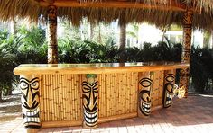 tiki bar with laughing tiki totems ~  Tiki bar = always makes me smile!