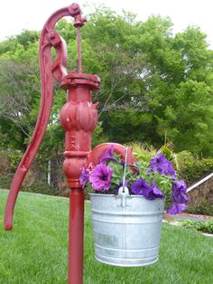 A pail of petunias on the old water pump.