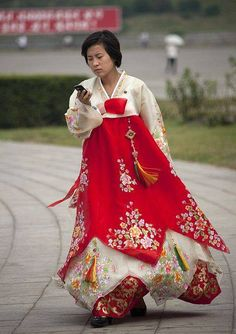 Woman in traditional dress checks her cell phone.