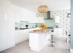 This retro Orla Kiely wallpaper transforms the white space in this open-plan kitchen