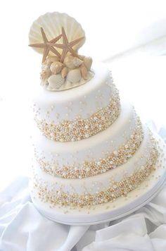 Pastel de boda con detalles marinos: conchas, estrellas de mar, perlas, blanco