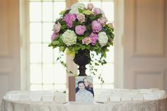 Chris and Kelli's guest book featured a photo of the couple on the cover. Escort cards were arranged on either side of a towering centerpiece comprised of pink peonies, white hydrangea blossoms, blush roses, and cascading greenery. #placecardtable #guestbook Photography: Vanessa Joy Photography. Read More: http://www.insideweddings.com/weddings/a-garden-inspired-summer-wedding-at-a-golf-club-in-new-jersey/631/