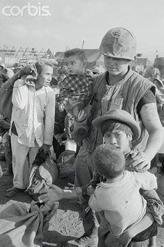 22 Jan 1968, Khe Sanh, South Vietnam --- Civilians Evacuated from Khe Sanh. Khe Sanh, South Vietnam: A US Marine escorts three Vietnamese children during evacuation of some 12,000 civilians from Khe Sanh village, January 22, in preparation for a major Communist offensive expected in the area just below the Demilitarized Zone.