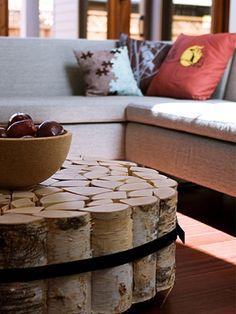 Couchtisch mal anders – ein super Deko-Tipp! Ein paar Birken-Holzpflöcke mit einem Umzugsgurt zusammengebunden, ein paar Rollen darunter befestigen und fertig ist der individuelle Couchtisch.